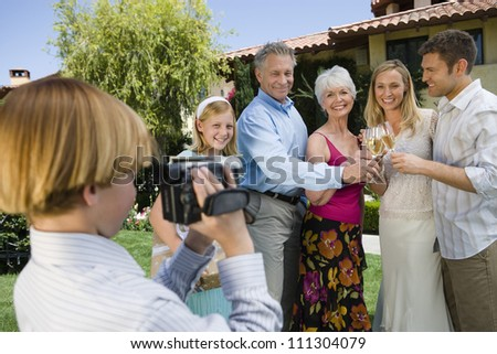 Teenage boy recording happy moments of family celebrating together at garden