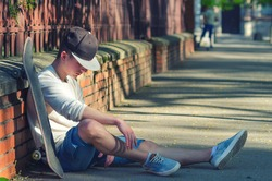 Teenage boy resting after skateboarding on sunny summer day.