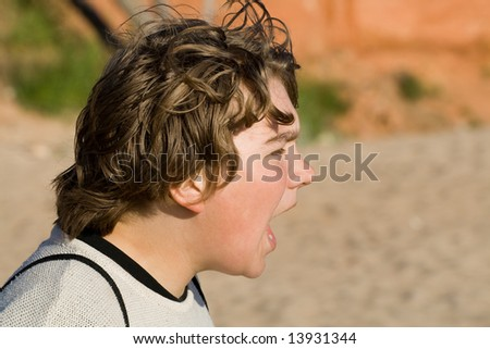 Teenage boy shouting. Beach sand and red sanstouns in background