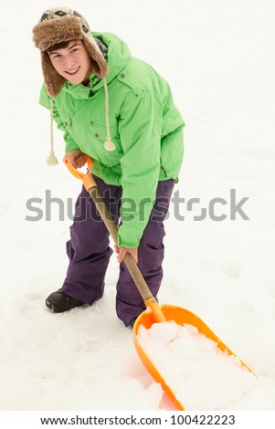 Teenage Boy Shovelling Snow From Path