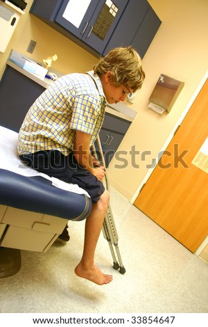 Teenage boy sitting on an examining table holding his crutches as he awaits the doctor's arrival.