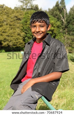 Teenage boy sitting on fence in bright countryside sunshine