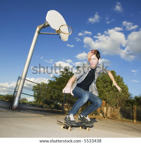Teenage boy skateboarder with his board.