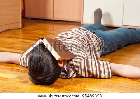 Teenage boy sleeping on the floor with book covering his face.