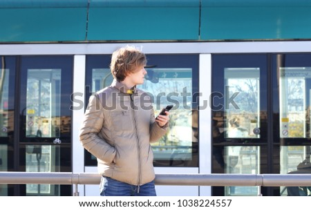 Teenage boy typing text message.Using smart phone.Tram station #1038224557