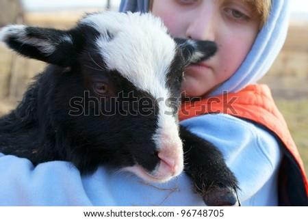 teenage boy with cute black lamb