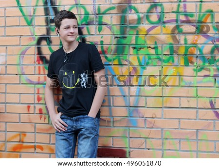 Teenage boy with ear-phones having fun, listen to music and relax over brick wall with graffito drawing, outdoor portrait - Shutterstock ID 496051870