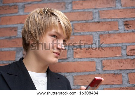 Teenage boy with mobile phone by brick wall, low angle