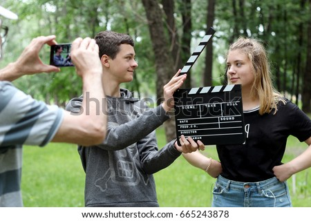 Teenage boy with realistic clapper cinema board ready to record a fun video with student girl in the park, a senior man holding smartphone to make a video, education and technology, outdoor summer