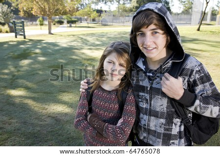 Teenage boy (15 years) with arm around younger sister (11 years), with bookbags at school