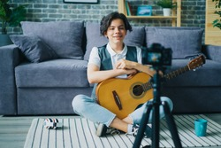 Teenage boy young vlogger is recording video for online vlog holding guitar talking smiling using modern camera. People, youth and vlogging concept.