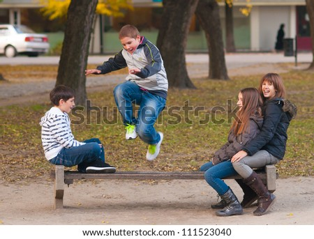 Teenage boys and girls having fun in the park on beautiful autumn day.
