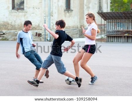 Teenage boys and girls playing soccer on the playground.