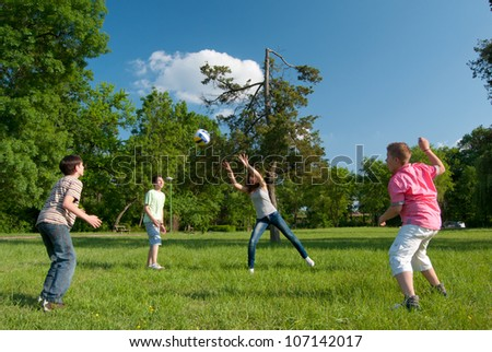 Teenage boys and girls playing with the ball in the park on sunny spring day.