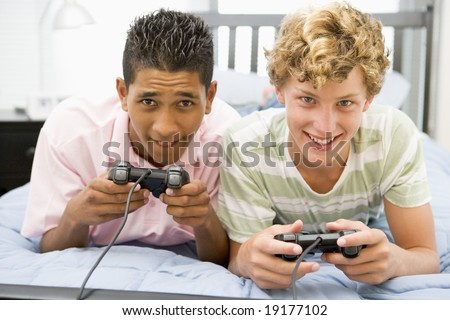 Teenage Boys Lying On Bed Playing On A Games Console