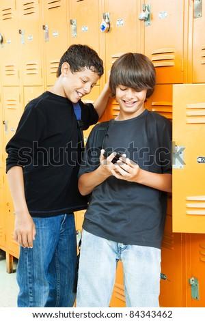 Teenage boys playing video games between classes in school. - stock photo