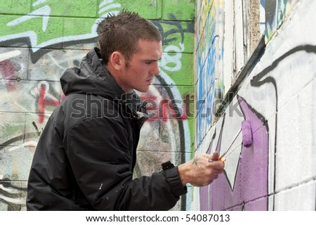 teenage boys tagging painting graffiti