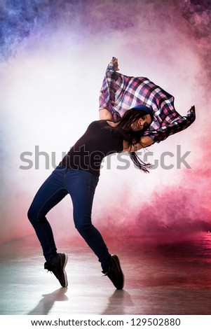 Teenage brakedancer girl in passionate dance pose with smoke on background