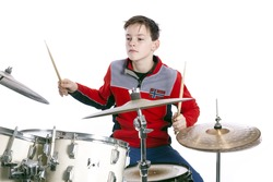 teenage caucasian boy plays drums in studio with white background