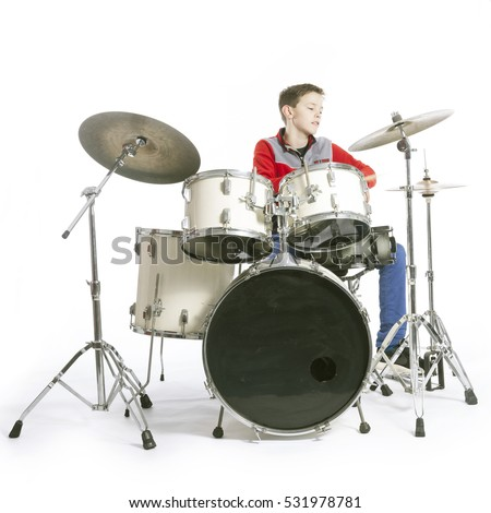 teenage caucasian boy plays drums in studio with white background #531978781