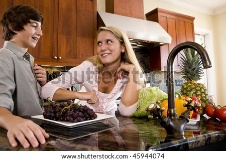 Teenage children in kitchen with fruits and vegetables on counter