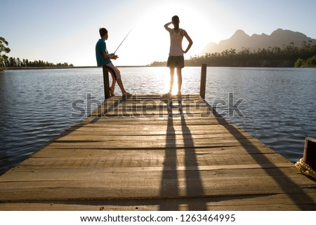 Teenage couple fishing in lake from wooden jetty