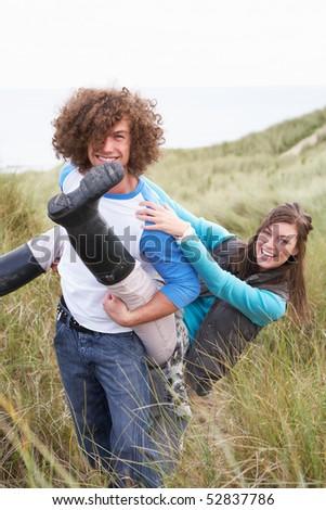 Teenage Couple Having Piggy Back Ride In Sand Dunes