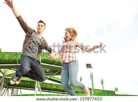 Teenage couple holding hands and jumping up in the air next to an attractions ride in an amusement park arcade during a sunny day.