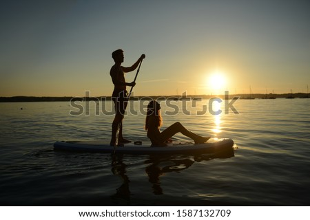 Teenage couple paddle boarding at sunset on Lake Starnberg, Bavaria, Germany, Europe