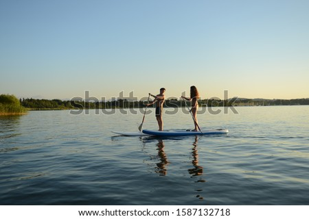 Teenage couple paddle boarding on Lake Starnberg, Bavaria, Germany, Europe