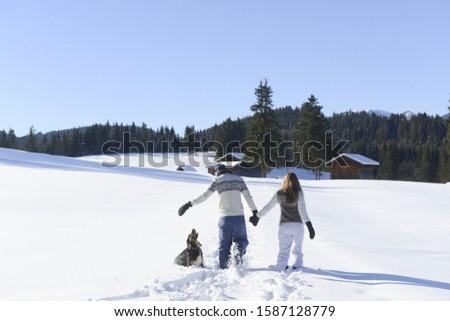 Teenage couple walking pet dog through snow at resort