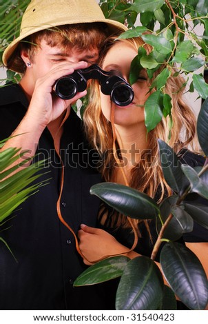 Teenage couple wearing safari hat with binoculars adventuring in the jungle