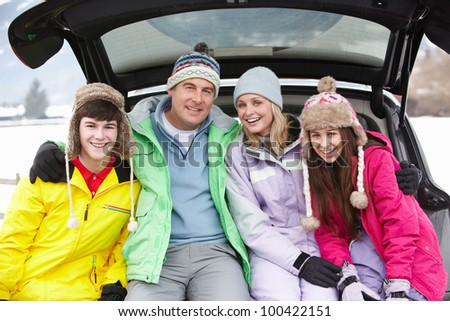 Teenage Family Sitting In Boot Of Car Wearing Winter Clothes