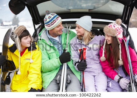 Teenage Family Sitting In Boot Of Car With Skis - stock photo