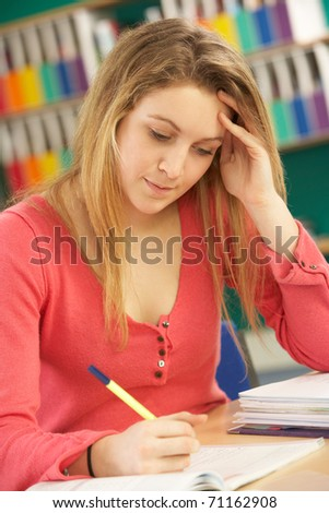 Teenage Female Student In Working In Classroom