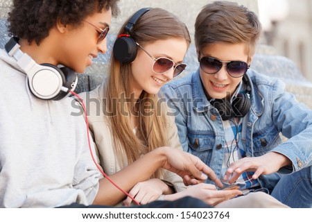 Teenage Friends. Three Cheerful Teenage Friends Sitting Close To Each Other And Listening To The Music