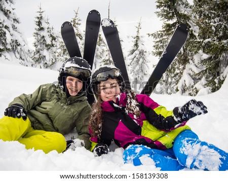 Teenage girl and boy skiing  - stock photo