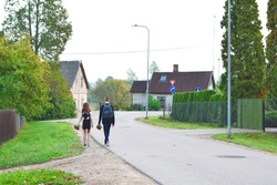 Teenage girl and boy walking and talking together on way to school wearing backpacks and holding  bouquet of red flowers for teacher in first school day 1th september back view. Back to school concept