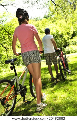 Teenage girl and her father with bicycles in summer park