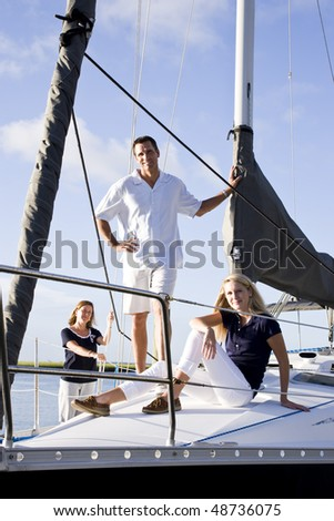 Teenage girl and parents relaxing on sailboat at dock on sunny day