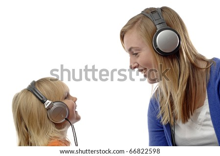Teenage girl and toddler use headsets to listen music.
