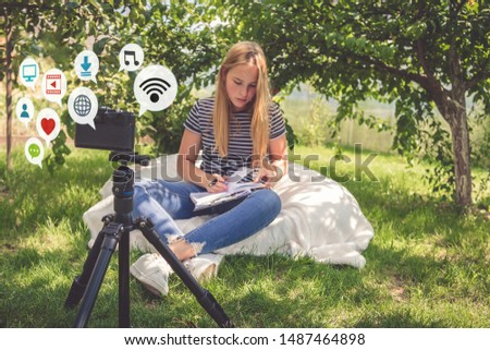 Teenage girl blogs online broadcasting video recording on the camera in nature, ideas of youth hobbies, freelancing, earning on a hobby generation z, online training and recording webinars #1487464898