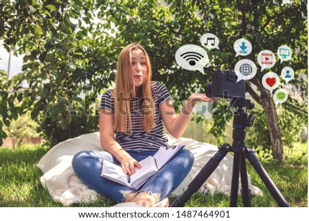 Teenage girl blogs online broadcasting video recording on the camera in nature, ideas of youth hobbies, freelancing, earning on a hobby generation z, online training and recording webinars #1487464901