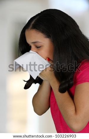 Teenage girl blowing her nose with tissue