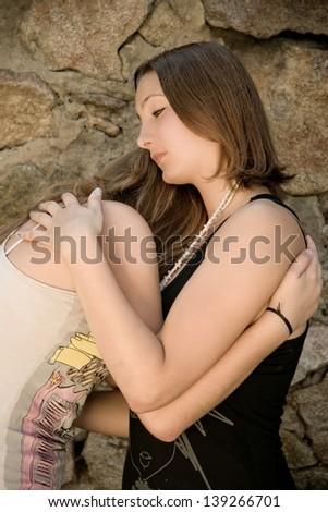 Teenage girl comforting crying friend with warm hug