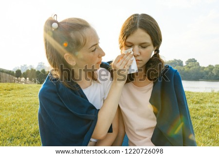 Teenage girl comforts her crying, upset, sad friend. The girls are sitting on the green grass in the park.