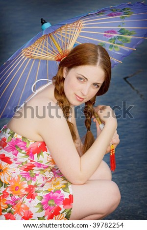 Teenage girl crouches and holds a flowered parasol while looking at the camera. Vertical format.