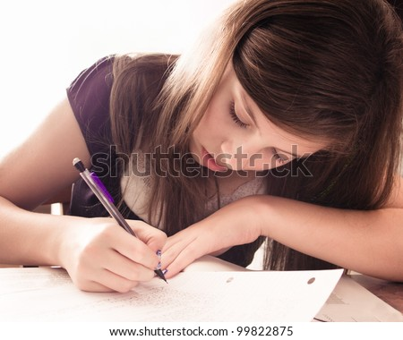 Teenage girl doing homework for school.  This is image is high key.