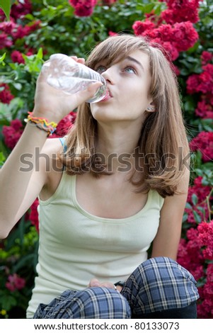 Teenage girl drinking water from the bottle in the flower garden