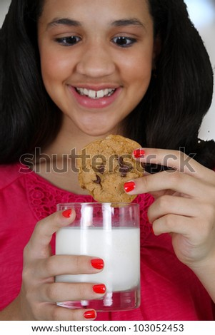 Teenage girl eating a cooking with milk